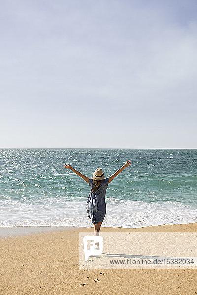 Rückansicht einer Frau  die ihre Arme am Strand hebt  Nazare  Portugal