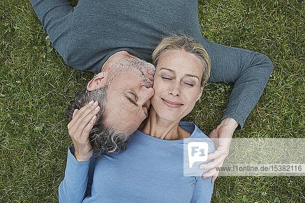 Draufsicht auf ein liebevolles reifes Paar  das im Gras liegt