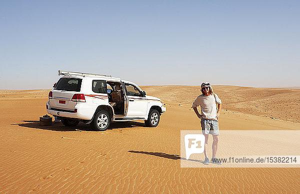 Tourist steht in der Wüste neben einem Geländewagen  Wahiba Sands  Oman