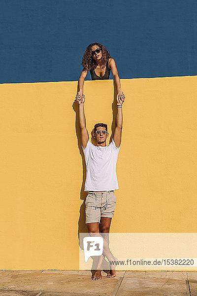 Junger Mann und Frau hinter einer gelben Wand halten sich an den Händen