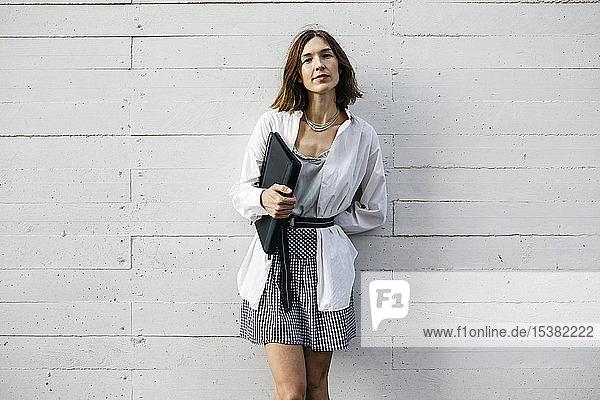 Hübsche Frau steht vor dem Gebäude und trägt eine Mappe