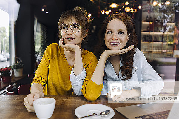 Two female friends with laptop in a cafe