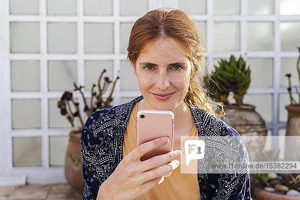 Porträt einer lächelnden rothaarigen jungen Frau mit Handy auf der Terrasse