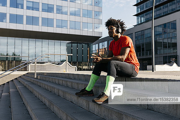 Young sportsman sitting on steps  listening to music