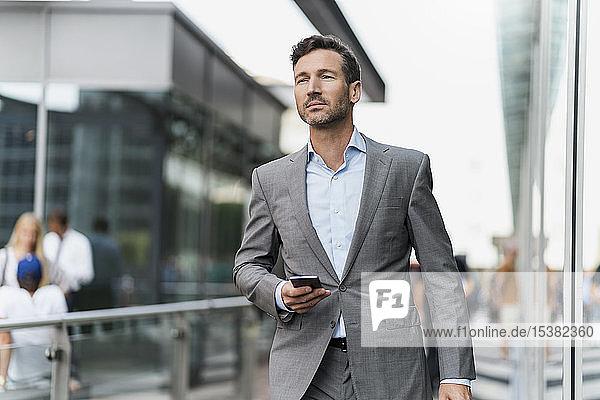 Porträt eines Geschäftsmannes mit Handy unterwegs