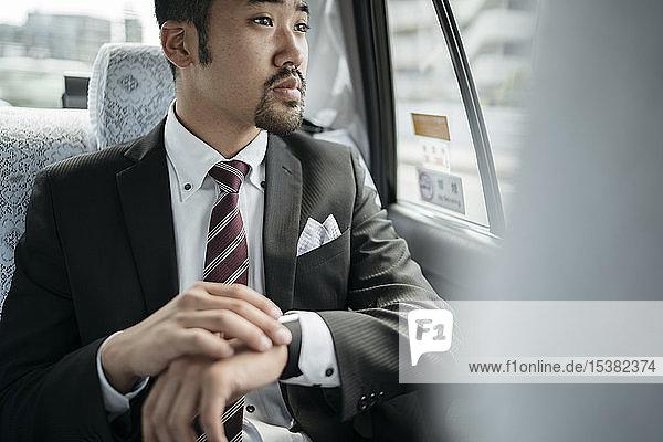 Junger Geschäftsmann in einem Taxi  der die Uhrzeit überprüft und aus dem Fenster schaut