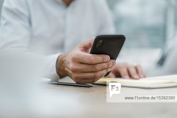 Nahaufnahme eines Geschäftsmannes mit Notebook und Handy