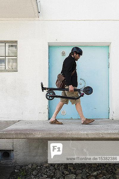 Mann mit Fahrradhelm trägt gefalteten Elektroroller