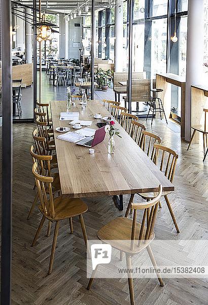 Laptop und Bücher auf dem Tisch in einem modernen Café