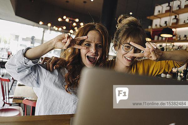 Zwei verspielte Freundinnen mit Laptop in einem Cafe