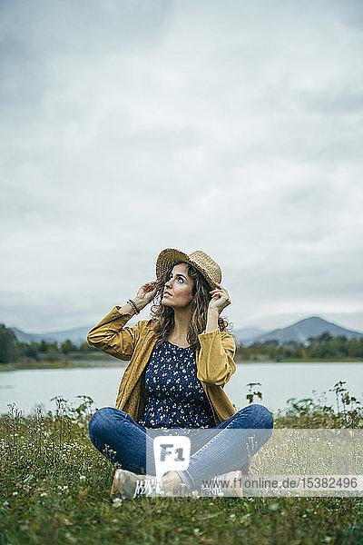 Junge Frau in gelbem Mantel sitzt auf einer Wiese und schaut auf