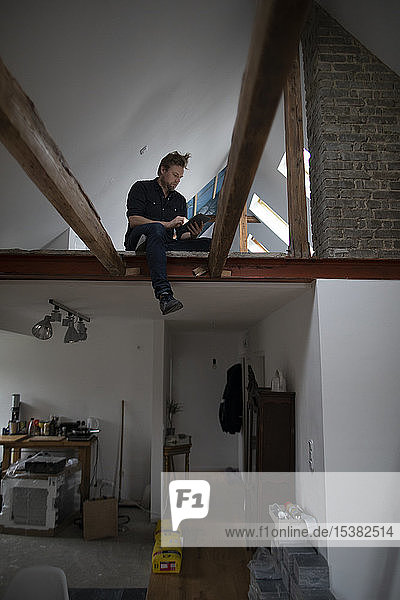 Architect working on construction sit of a loft conversion  sitting in truss