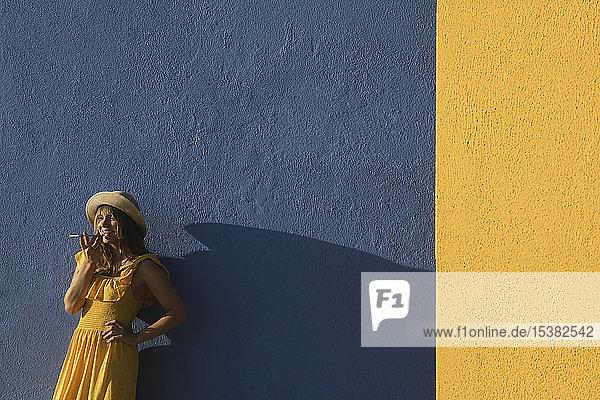 Frau in einem gelben Kleid mit Smartphone vor gelben und blauen Wänden