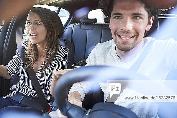 Geschocktes Ehepaar in einem Auto mit fahrendem Mann