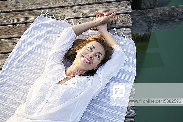 Smiling mature woman lying on a towel on a jetty at a lake