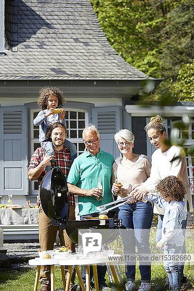 Glückliche Großfamilie beim Grillen im Garten