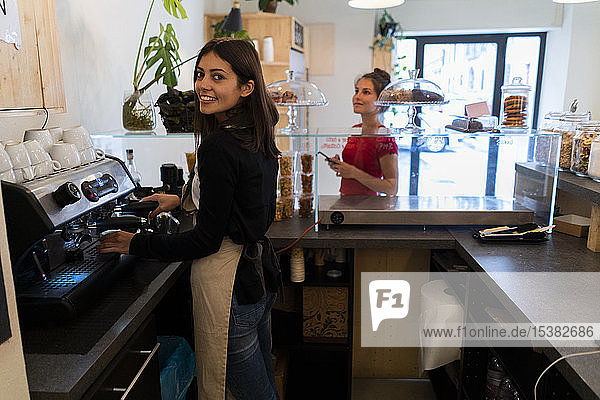 Portrait of smiling young woman preoaring a coffeer in a cafe