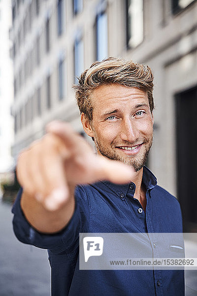 Portrait of confident young man in the city pointing his finger