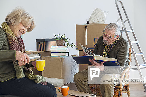 Senior couple with photo album and hot drink surrounded by cardboard boxes in an empty room