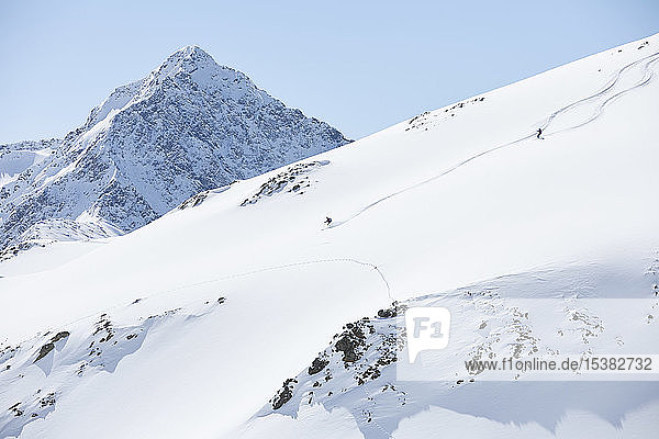 Two skiers riding downhill in the mountains  Kuehtai  Tyrol  Austria