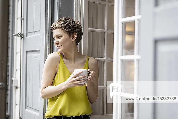 Lächelnde Frau mit einer Tasse Kaffee an der Terrassentür
