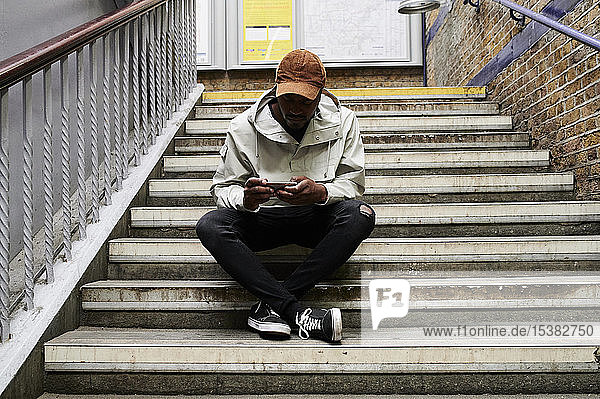 Man sitting on stairs looking at cell phone