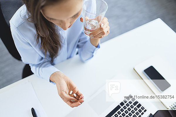 Overhead view of woman taking painkillers while sitting on office