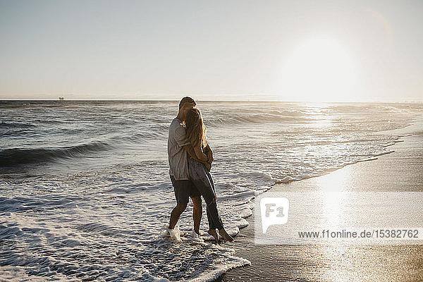 Liebenswertes junges Paar umarmt sich bei Sonnenuntergang am Meeresufer