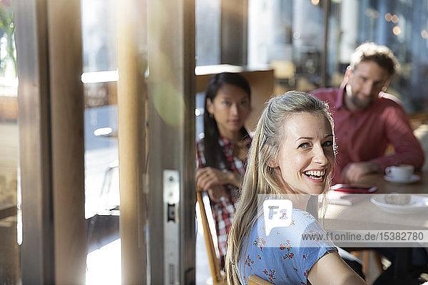 Porträt einer glücklichen Frau mit Freunden in einem Cafe