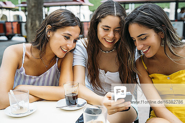 Three happy female friends sharing cell phone at a cafe in the city