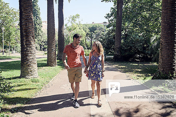 Smiling young couple walking hand in hand through a park