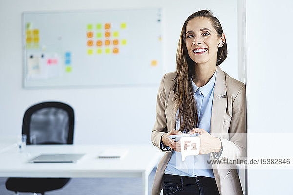 Young businesswoman standing in office holding phone and smiling at camera