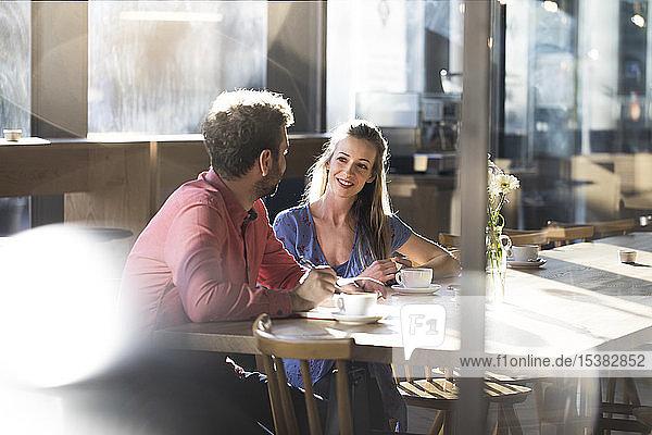 Frau und Mann unterhalten sich am Tisch in einem Cafe