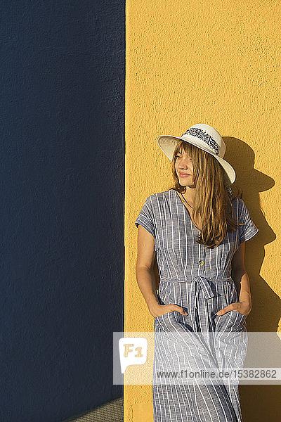 Frau steht vor gelben und blauen Mauern
