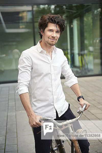 Porträt eines selbstbewussten Mannes mit altem Fahrrad in der Stadt