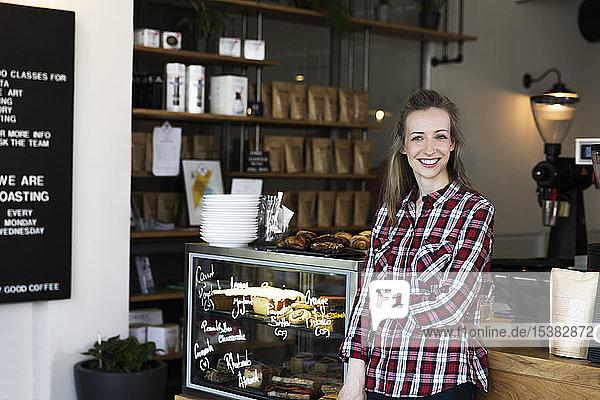 Porträt einer lächelnden Frau an der Theke eines Cafés