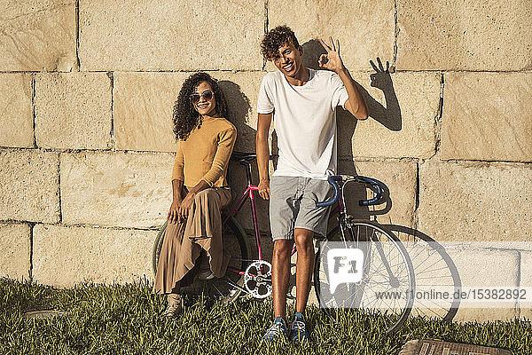 Junges Paar mit Fahrrad  an Steinmauer gelehnt  Handzeichen machen Junges Paar mit Fahrrad, an Steinmauer gelehnt, Handzeichen machen