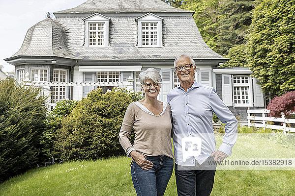 Glückliches älteres Ehepaar steht im Garten seines Hauses