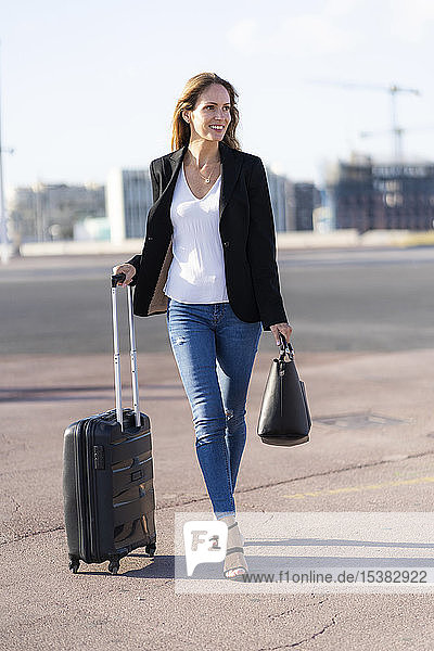 Lächelnde Geschäftsfrau mit Gepäck unterwegs