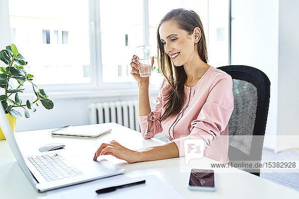 Lächelnde junge Frau arbeitet am Laptop im Home-Office