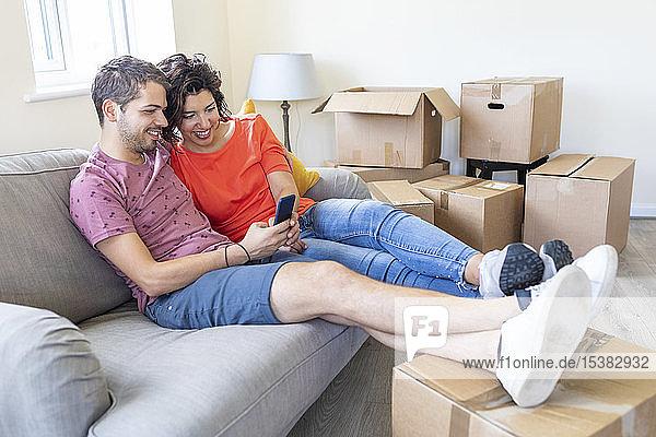 Glückliches Paar benutzt Handy auf der Couch im neuen Zuhause
