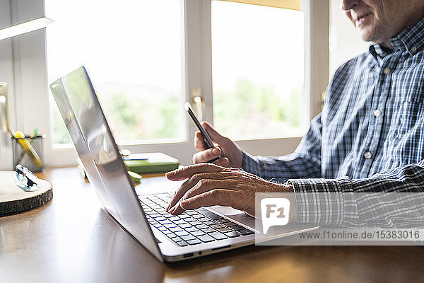 Senior man using laptop and smartphone at home