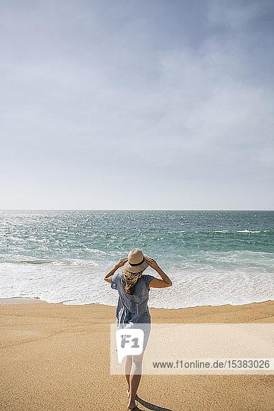 Rückansicht einer Frau  die am Strand spazieren geht  Nazare  Portugal