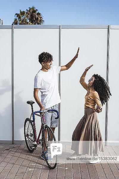 Glückliches Paar mit Fahrrad vor weißem Zaun stehend  High-Five Glückliches Paar mit Fahrrad vor weißem Zaun stehend, High-Five