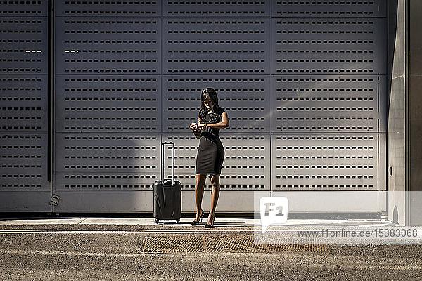 Geschäftsfrau mit Einkaufswagen  die die Zeit überprüft