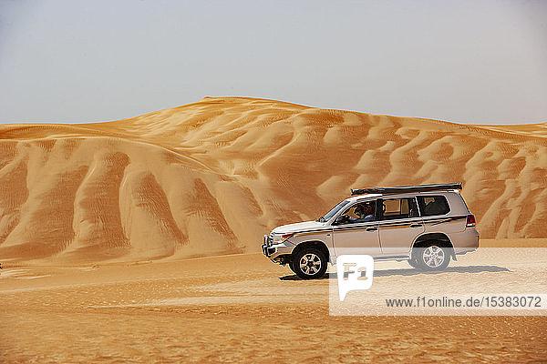 Tourist fährt in der Wüste im Geländewagen,  Wahiba Sands,  Oman