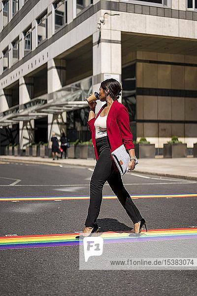 Geschäftsfrau  die Kaffee zum Mitnehmen trinkt  während sie auf LGBT-Streifen über die Straße geht  London  UK