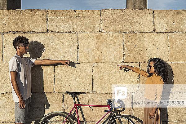 Junges Paar steht vor der Wand und zeigt aufeinander Junges Paar steht vor der Wand und zeigt aufeinander
