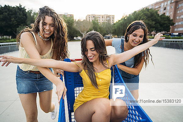 Three playful female friends with shopping cart in the city