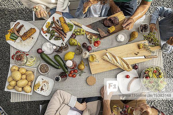 Draufsicht auf die Familie beim Mittagessen im Garten